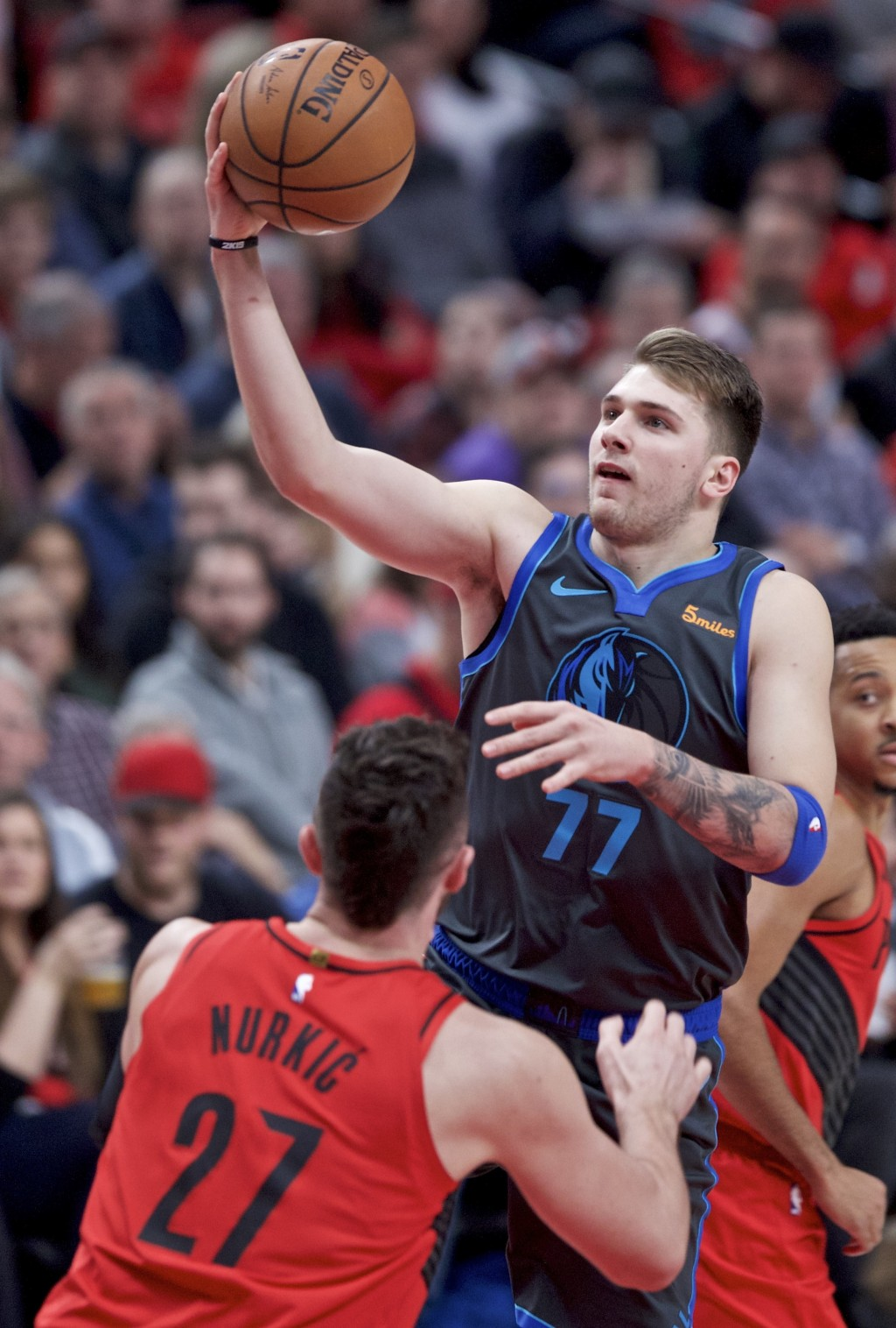 Dallas Mavericks forward Luka Doncic, right, shoots over Portland Trail Blazers center Jusuf Nurkic during the first half of an NBA basketball game in...