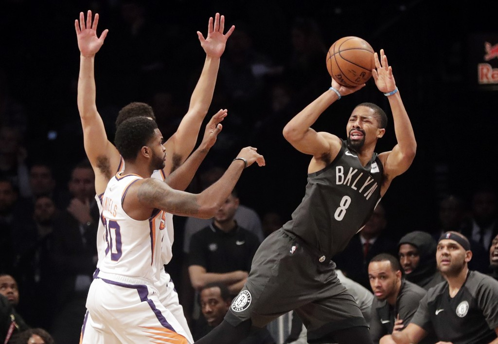 Brooklyn Nets' Spencer Dinwiddie (8) passes away from Phoenix Suns' Troy Daniels (30) during the first half of an NBA basketball game Sunday, Dec. 23,...