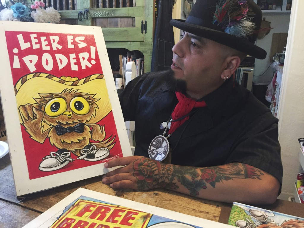 In this Thursday, April 5, 2018 photo artist Moises Salcedo of Albuquerque, who goes by the name El Moises, shows a panel of characters for the biling...