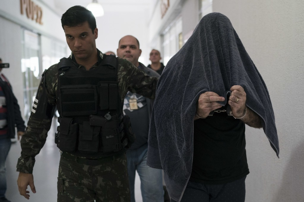 In this Aug. 2, 2018 photo, Army Sub Lieutenant Marco Antonio Gomes Sacramento, right, is escorted in handcuffs by a soldier after police arrested him...