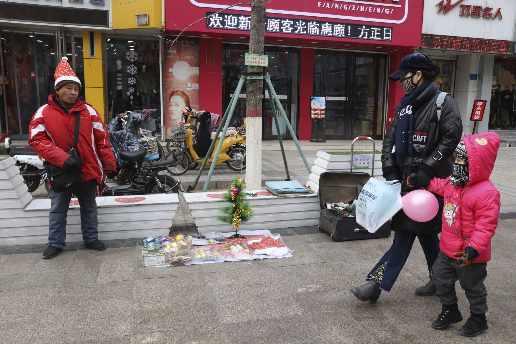 In this Saturday, Dec. 22, 2018, photo, a man sells Christmas decorations on a street of Zhangjiakou in northern China's Hebei province. At least thre...