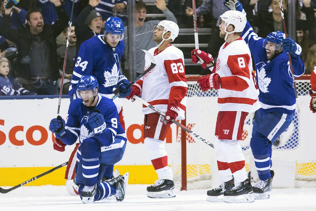 Toronto Maple Leafs' John Tavares, left, celebrates after scoring his team's game-tying goal against the Detroit Red Wings in the final seconds of thi...