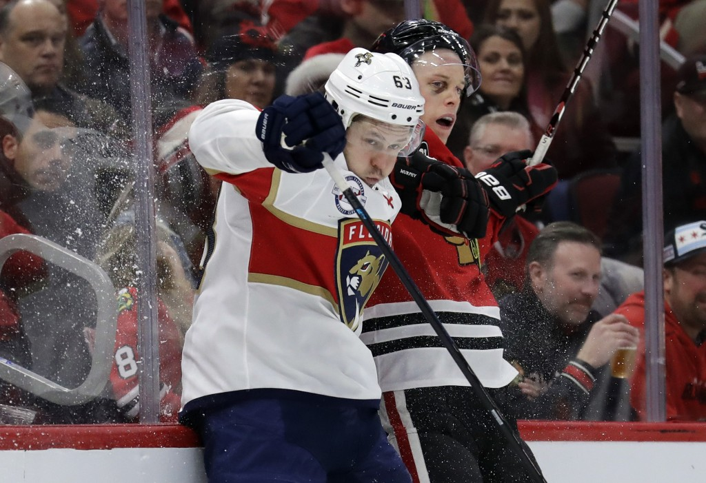Florida Panthers right wing Evgenii Dadonov, left, is checked by Chicago Blackhawks defenseman Connor Murphy during the second period of an NHL hockey...