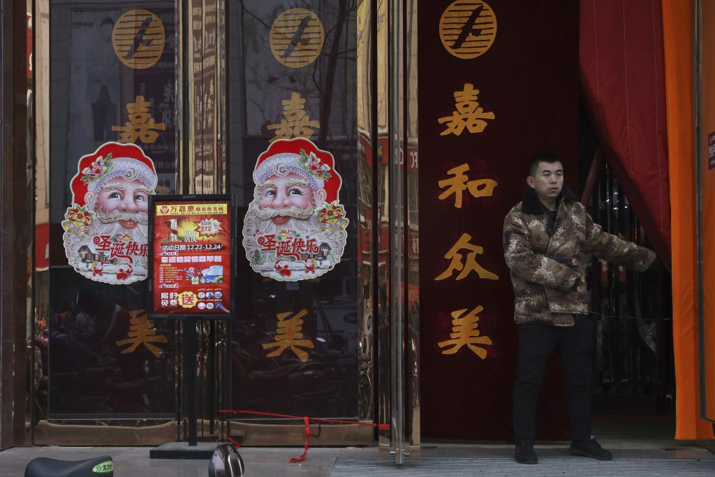 In this Saturday, Dec. 22, 2018, photo, a worker guards the entrance of a shop decorated with images of Santa Claus in Zhangjiakou in northern China's...
