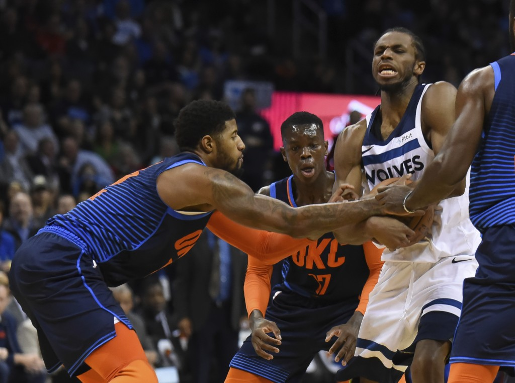 Oklahoma City Thunder forward Paul George, left, tries to get the ball away from Minnesota Timberwolves guard Andrew Wiggins, right, in the first half...