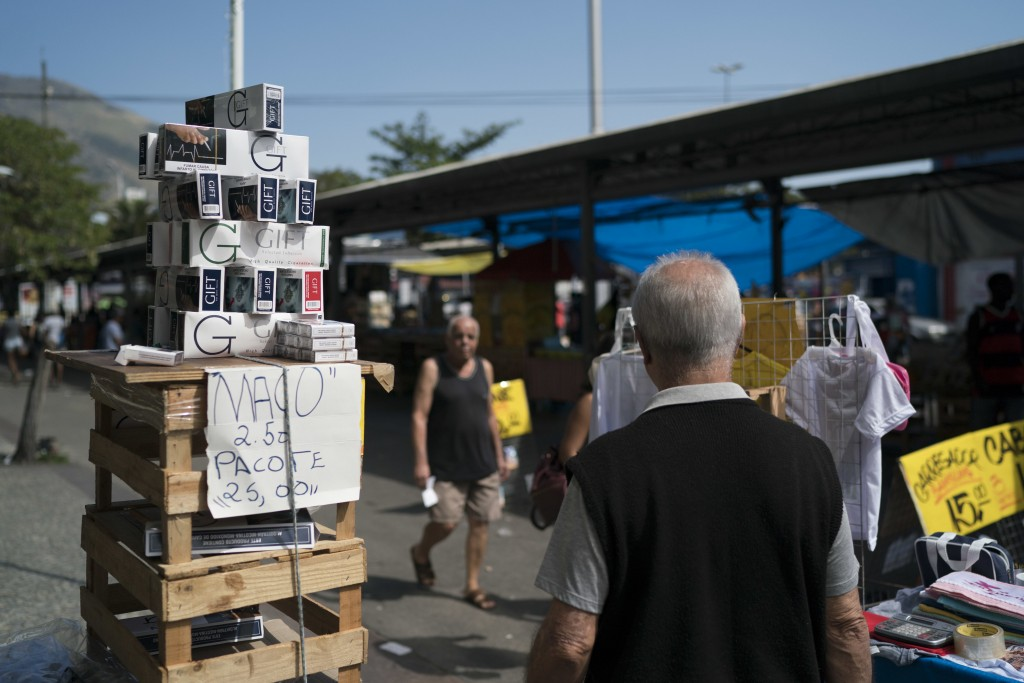 In this Aug. 24, 2018 photo, packs of illegal cigarettes stand for sale at a market in the Realengo neighborhood of Rio de Janeiro, Brazil. Militias b...