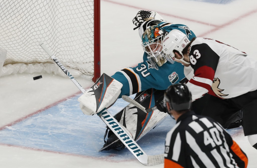 Arizona Coyotes' Conor Garland (83) scores against San Jose Sharks goaltender Aaron Dell (30) in the third period of an NHL hockey game in San Jose, C