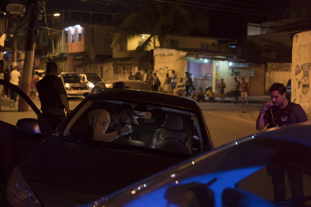 In this Aug. 31, 2018 photo, a forensic police officer inspects a car where the body of a man was found in Belford Roxo, greater Rio de Janeiro, Brazi...