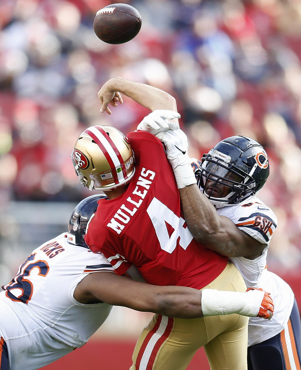 San Francisco 49ers quarterback Nick Mullens (4) is hit by Chicago Bears defensive end Akiem Hicks, left, and outside linebacker Khalil Mack during th...