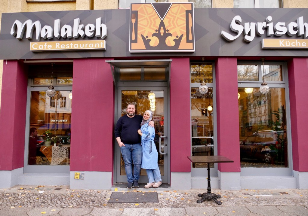 In this Nov. 9, 2018 photo Malakeh Jazmati and her husband Mohammad Al Ghamian pose outside her restaurant in Berlin, Germany. After fleeing her homel...