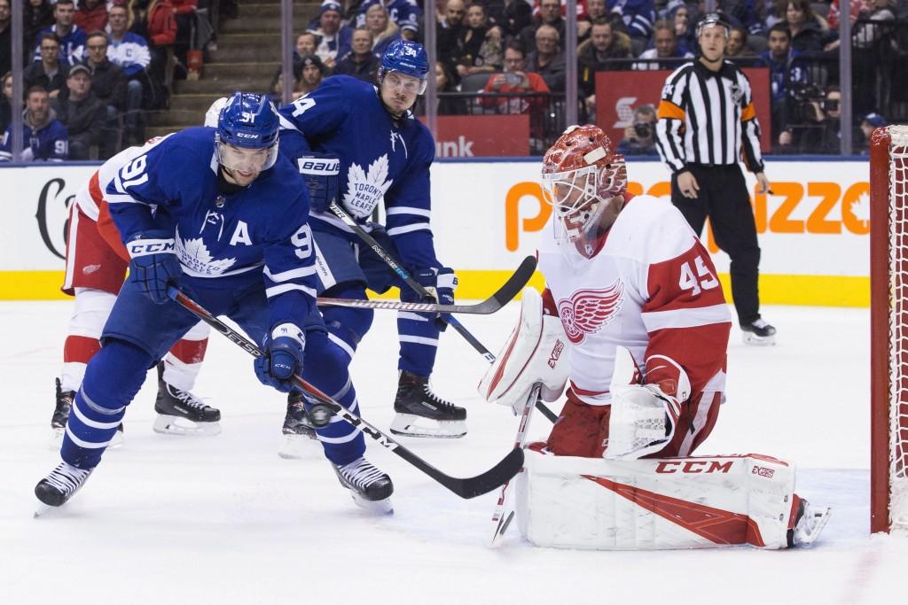 Toronto Maple Leafs John Tavares, left, attempts to tip the puck past Detroit Red Wings goaltender Jonathan Bernier as teammate Auston Matthews looks ...