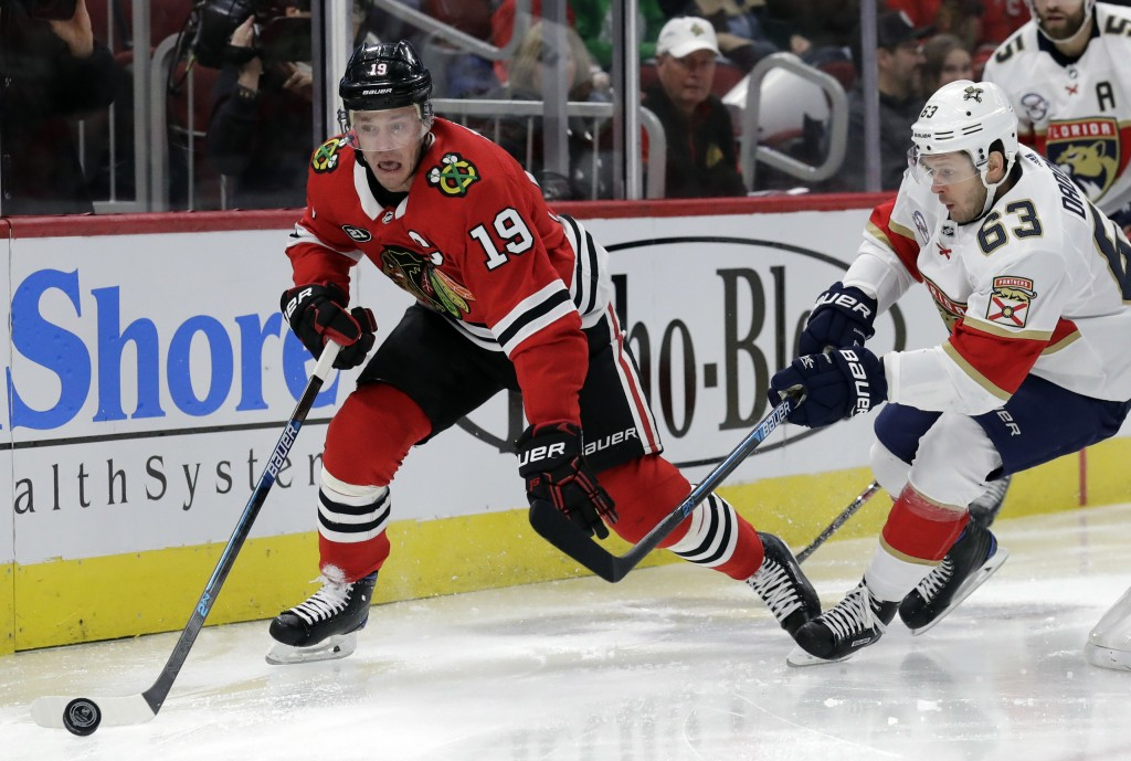 Chicago Blackhawks center Jonathan Toews, left, controls the puck against Florida Panthers right wing Evgenii Dadonov during the first period of an NH...