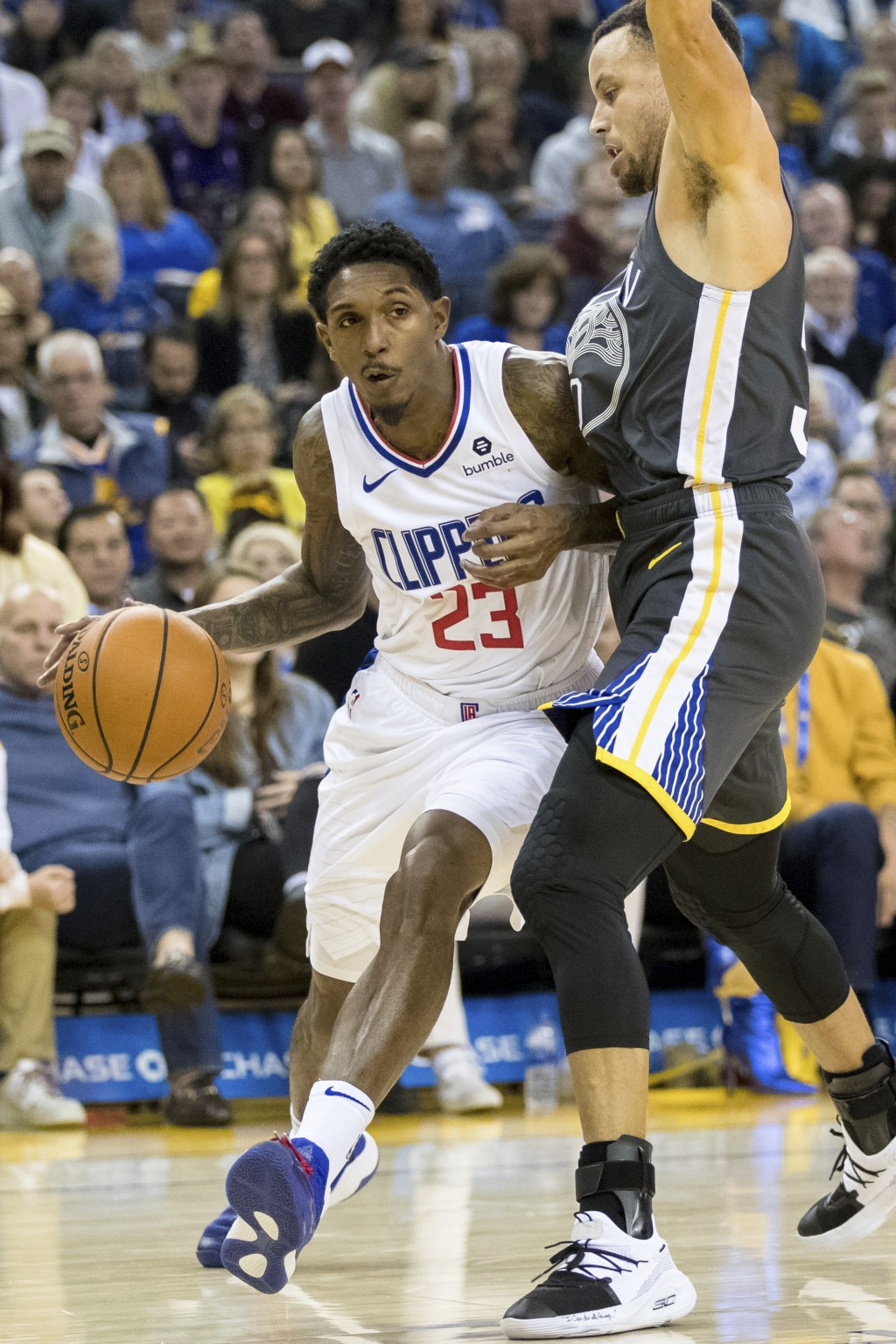 Los Angeles Clippers guard Lou Williams (23) dribbles as Golden State Warriors guard Stephen Curry defends in the second quarter of an NBA basketball ...