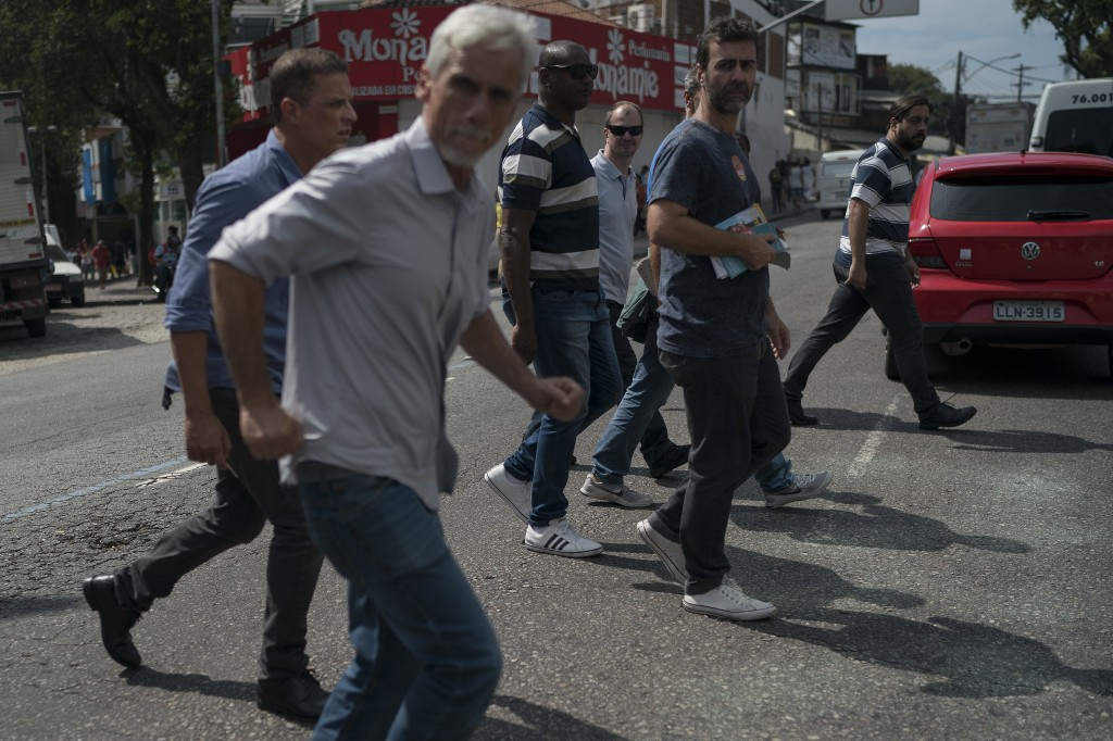 In this Aug. 24, 2018 photo, state legislator Marcelo Freixo, holding books, center right, crosses a street surrounded by security guards as he campai...