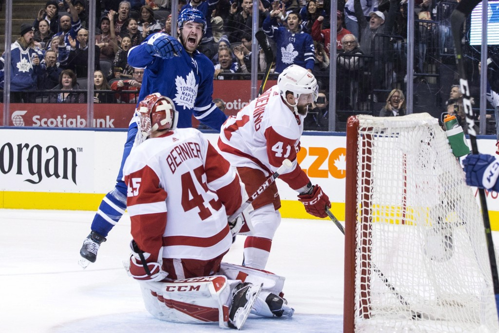 Detroit Red Wings' Luke Glendening (41) retrieves the puck from the net as Toronto Maple Leafs' Frederik Gauthier celebrates after scoring his team's ...