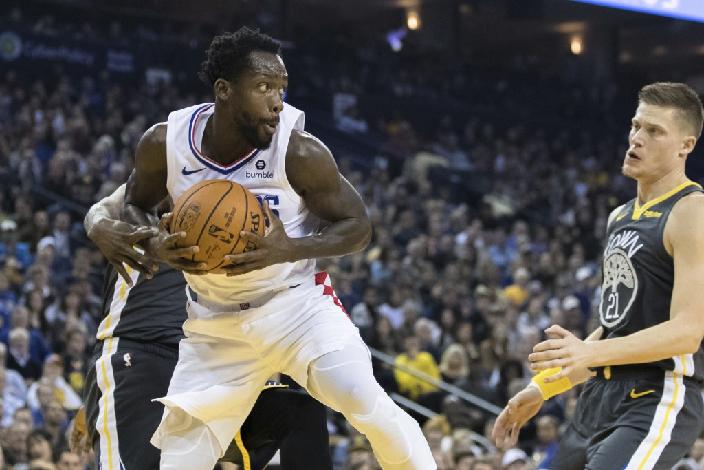 Los Angeles Clippers guard Patrick Beverley (21) gets a rebound against the Golden State Warriors in the first quarter of an NBA basketball game, Sund