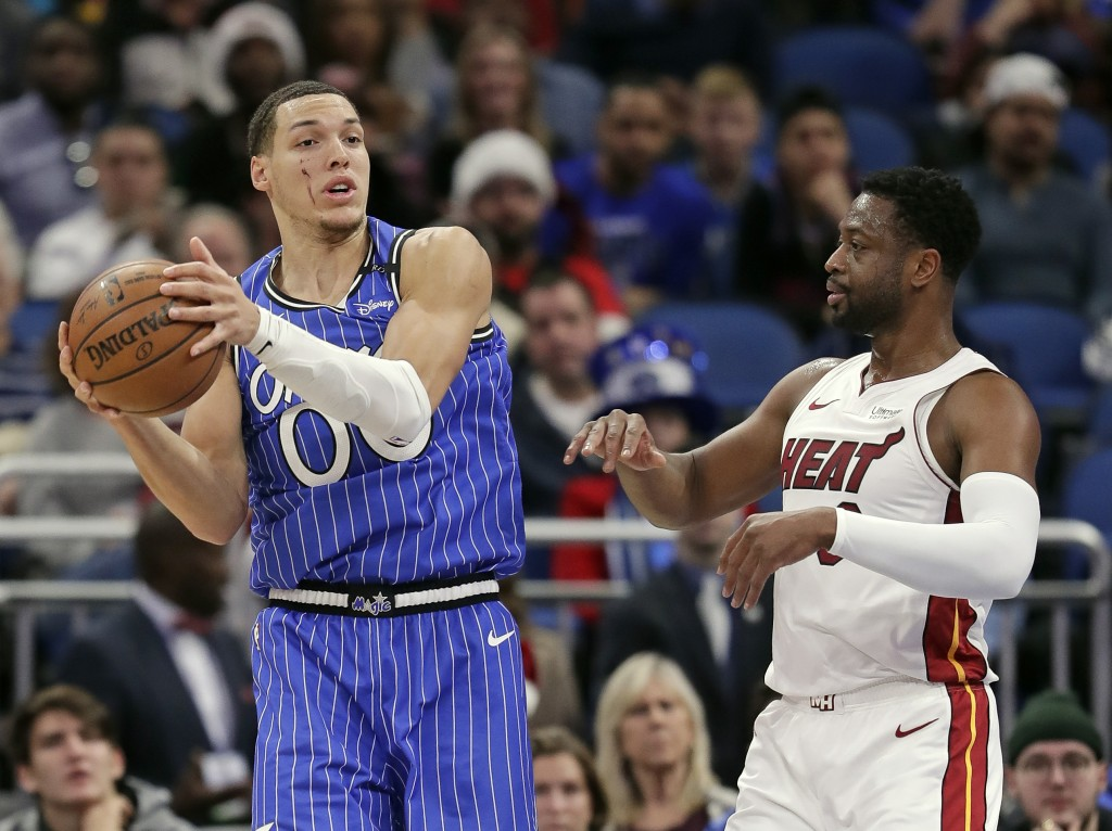 Orlando Magic's Aaron Gordon, left, looks to pass as he is defended by Miami Heat's Dwyane Wade during the first half of an NBA basketball game, Sunda...