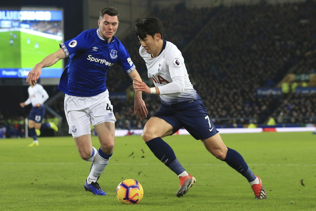 Everton's Michael Keane, left, and Tottenham's Son Heung-min vie for the ball during the English Premier League soccer match between Everton and Totte...