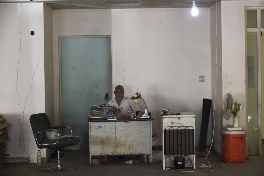 In this Thursday, Dec. 13, 2018 photograph, a man sits behind a desk in the closed Aden Governorate General Hospital in Aden, Yemen. Land mines scatte...