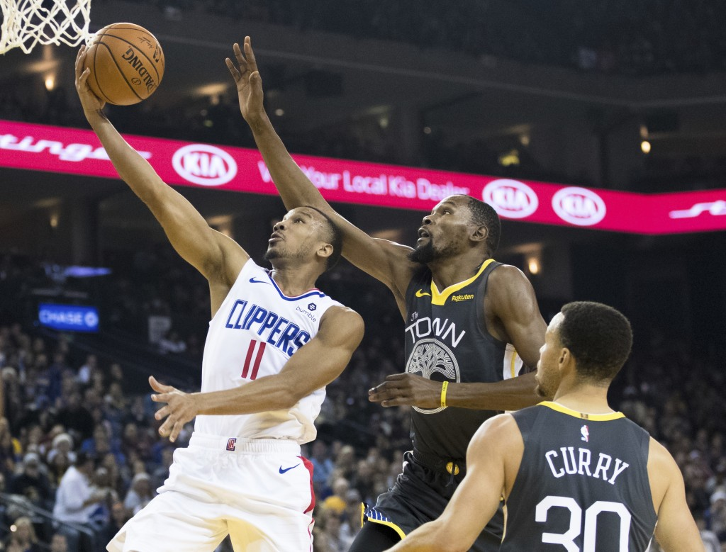 Los Angeles Clippers guard Avery Bradley (11) shoots as Golden State Warriors forward Kevin Durant defends in the first quarter of an NBA basketball g