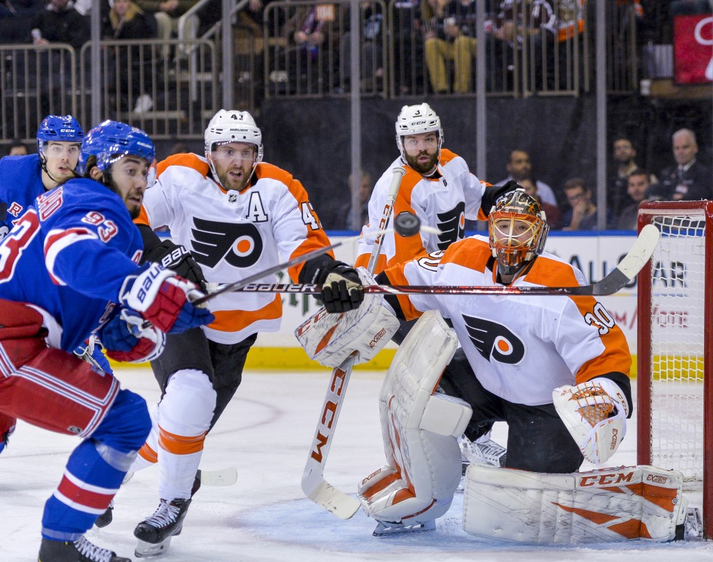 Philadelphia Flyers goaltender Michal Neuvirth (30) keeps his eyes on a flying puck during the second period of an NHL hockey game against the New Yor...