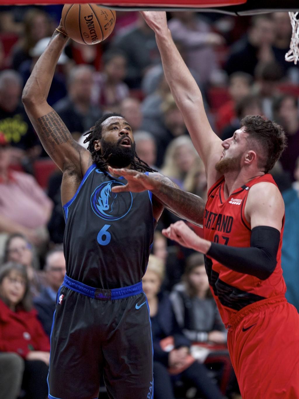 Dallas Mavericks center DeAndre Jordan, left, shoots over Portland Trail Blazers center Jusuf Nurkic during the first half of an NBA basketball game i...