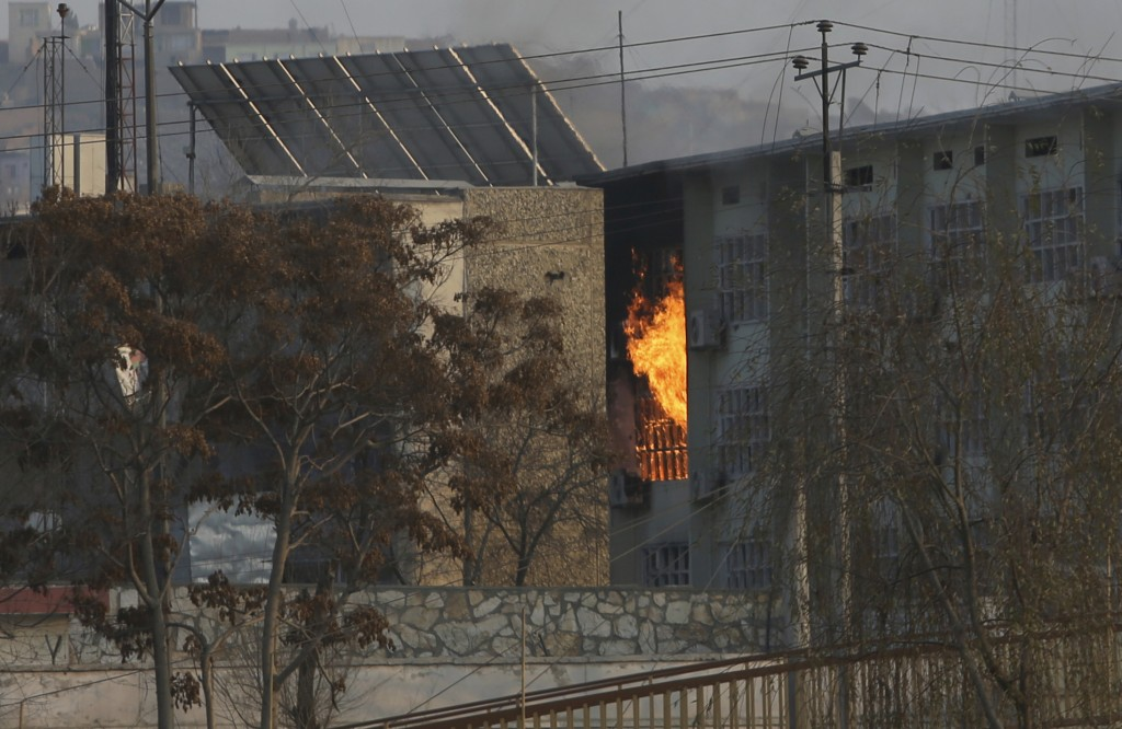 Flames rise from a government building after an explosion and attack by gunmen, in Kabul, Afghanistan, Monday, Dec. 24, 2018. (AP Photo/Rahmat Gul)