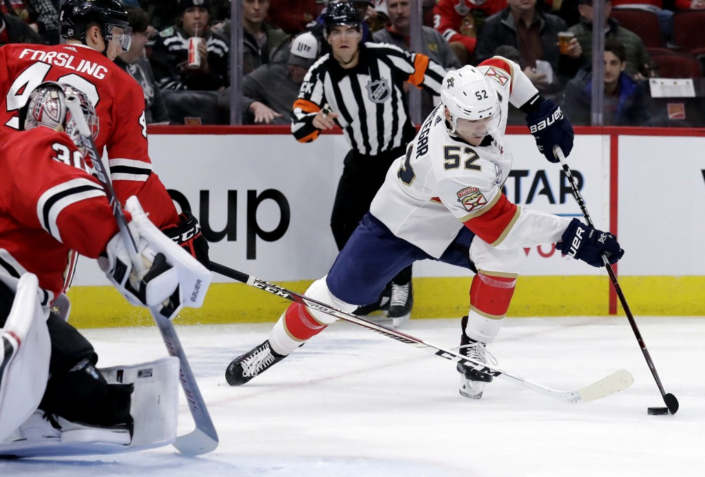 Florida Panthers defenseman MacKenzie Weegar, right, controls the puck against Chicago Blackhawks defenseman Gustav Forsling and goalie Cam Ward durin