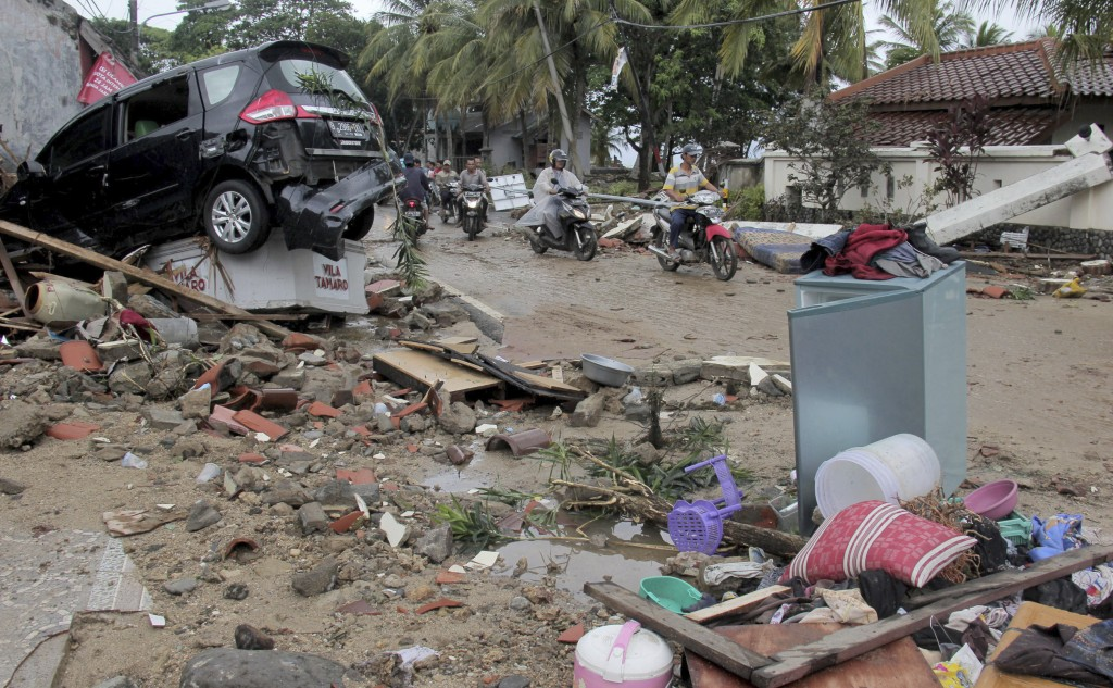 Motorists ride past debris following a tsunami in Anyar, Indonesia, Sunday, Dec. 23, 2018. An eruption of one of the world's most infamous volcanic is