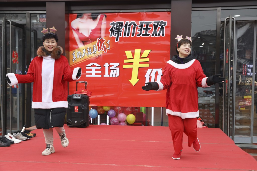 In this photo Saturday, Dec. 22, 2018, photo, sales staff from an apparel shop dance wearing Christmas themed costumes to promote a year end sales in ...