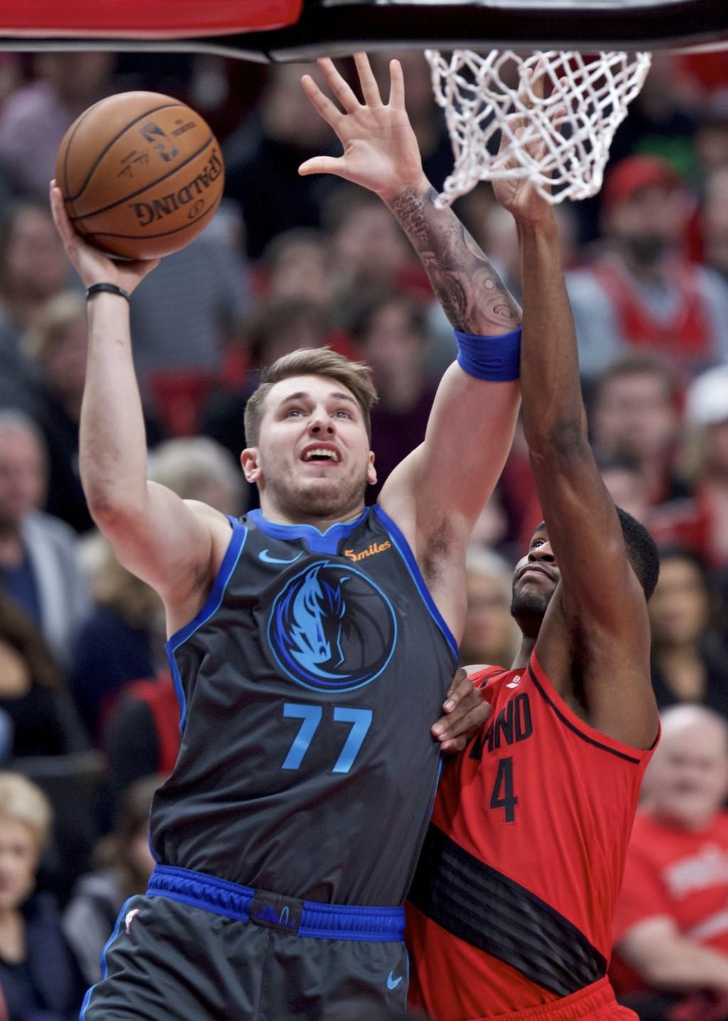 Dallas Mavericks forward Luka Doncic, left, shoots over Portland Trail Blazers forward Maurice Harkless during the first half of an NBA basketball gam...