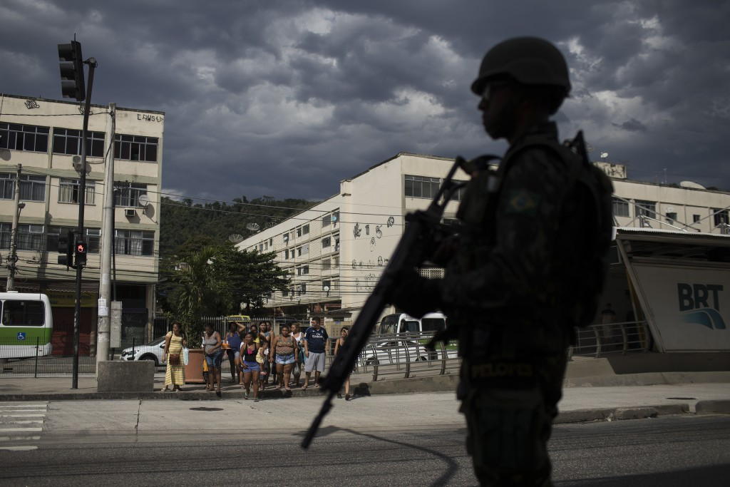 In this May 19, 2018 photo, a soldier patrols during an operation while pedestrians wait to cross the street in the Bateau Mouche slum of Rio de Janei...
