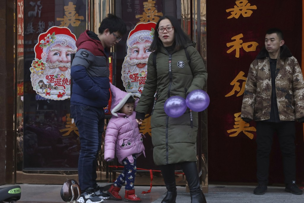 In this Saturday, Dec. 22, 2018, photo, a family walk past images of Santa Claus in Zhangjiakou in northern China's Hebei province. At least three Chi...