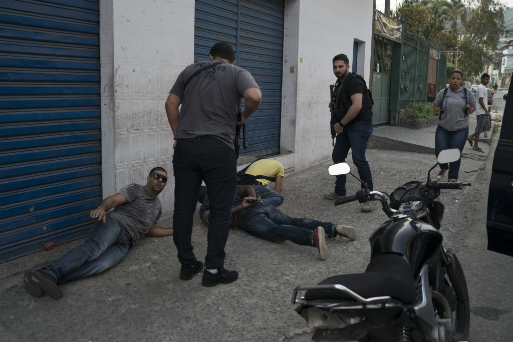 In this Sept. 3, 2018 photo, plained clothed police arrest three men suspected of being members of organized crime and an extortion group in Sao Gonca...