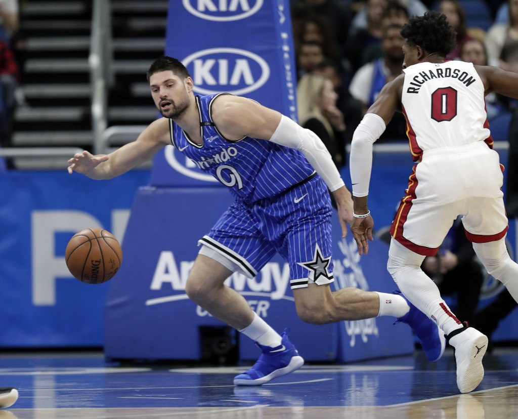 Orlando Magic's Nikola Vucevic, left, goes after a loose ball in front of Miami Heat's Josh Richardson (0) during the first half of an NBA basketball ...