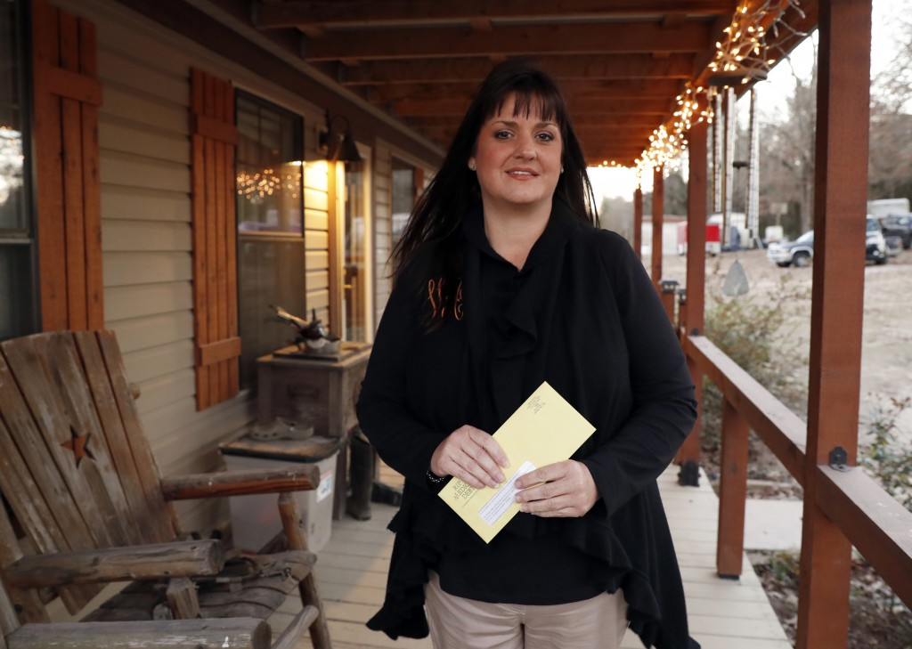 In this Thursday, Dec. 20, 2018 photo, Reagen Adair holds on to a RIP Medical Debt yellow envelope as she poses for a photo at her home in Murchison, ...