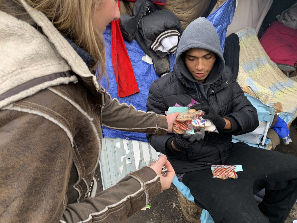 In this Dec. 13, 2018 photo, Kristina Tester, left, hands out cookies made by high school students to residents of a homeless camp made up mainly of N...