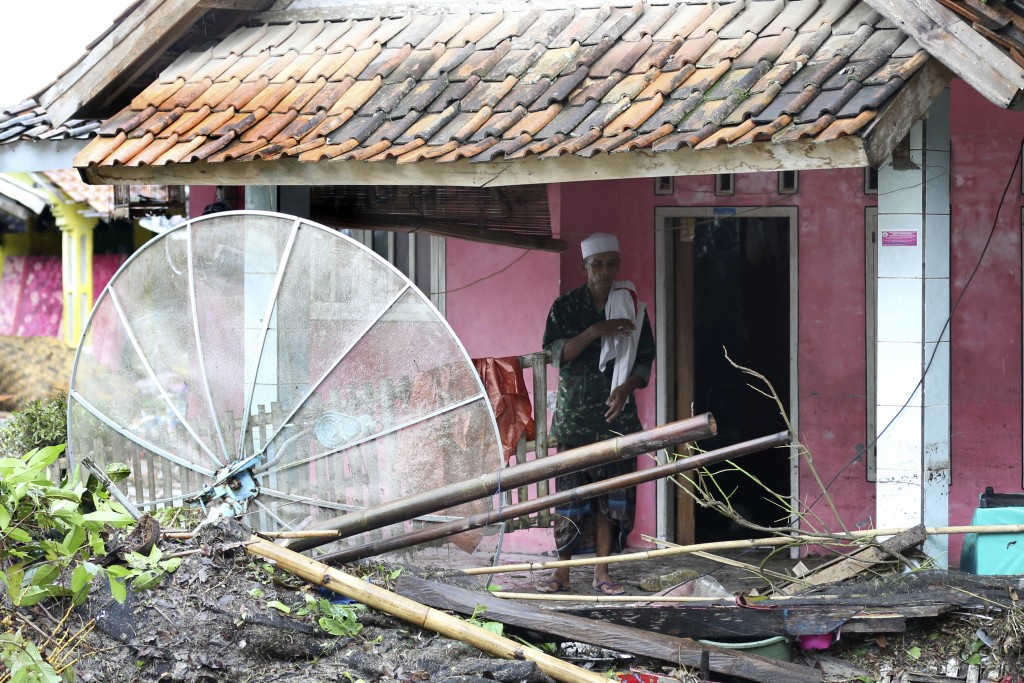 A resident inspects his house damaged by a tsunami, in Sumur village, Indonesia, Monday, Dec. 24, 2018. The tsunami apparently caused by the eruption