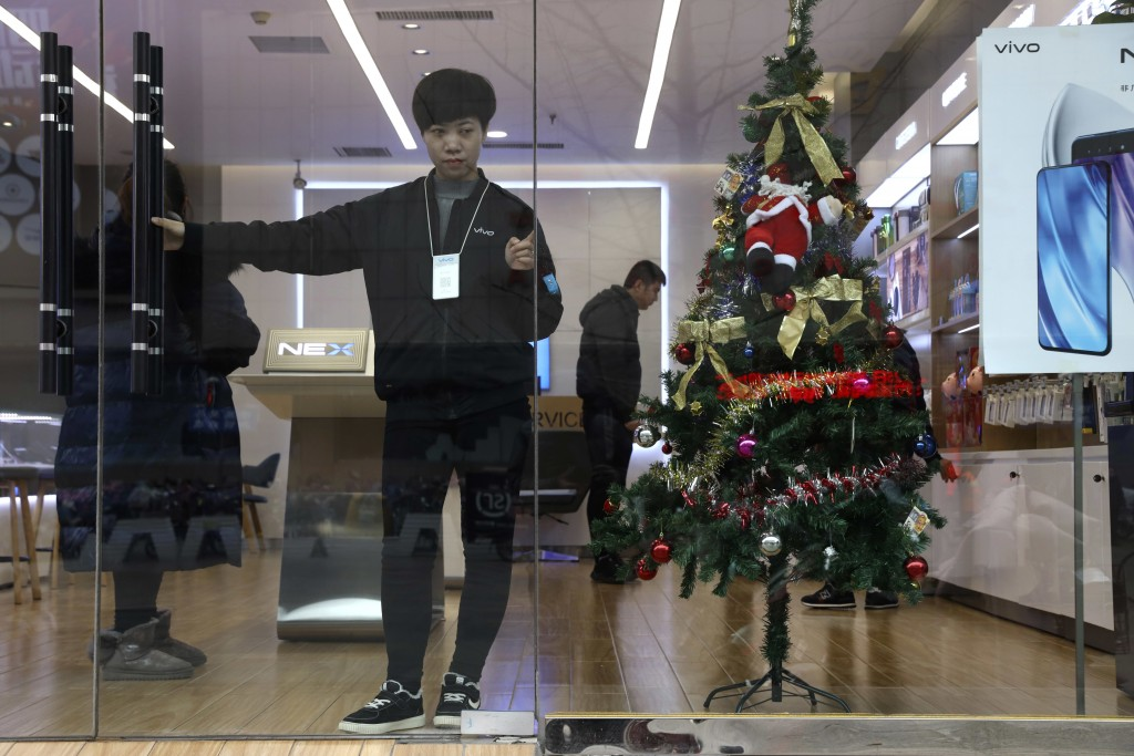 In this Saturday, Dec. 22, 2018, photo, a sales person waits for customers near a Christmas tree decoration in Zhangjiakou in northern China's Hebei p...