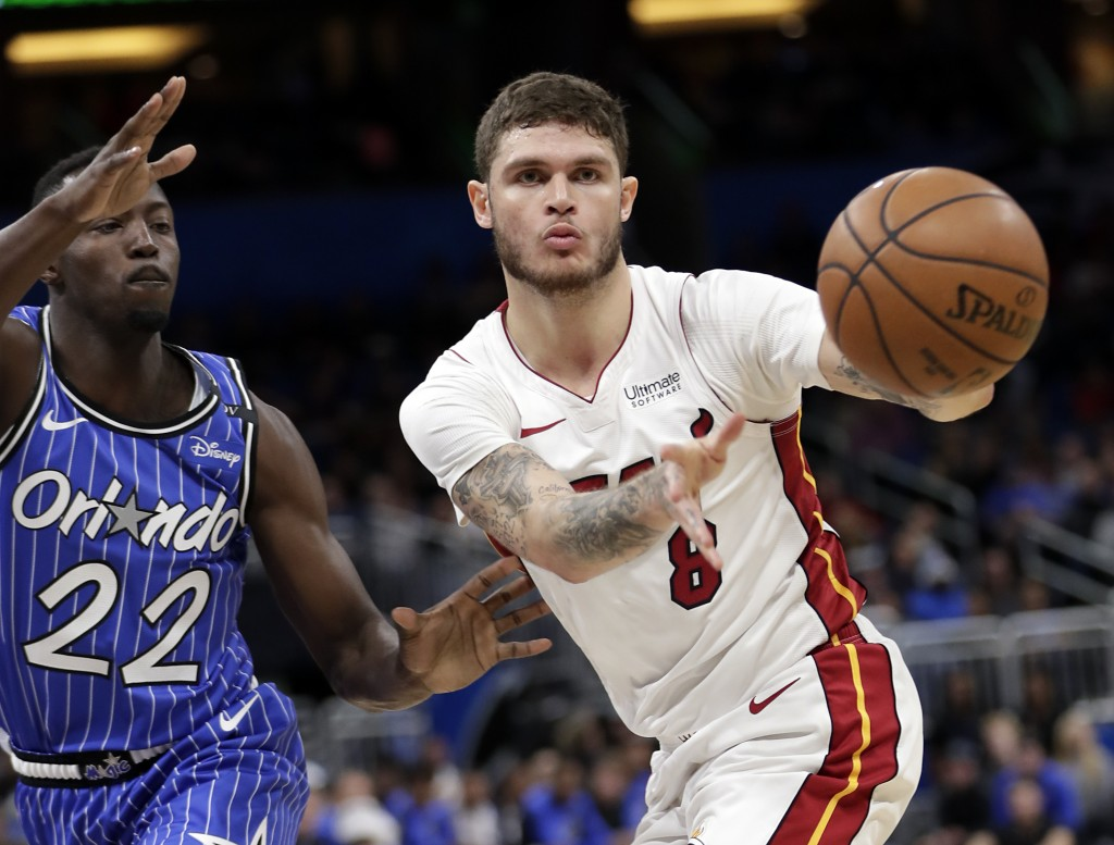 Miami Heat's Tyler Johnson (8) passes the ball as he is defended by Orlando Magic's Jerian Grant (22) during the first half of an NBA basketball game,