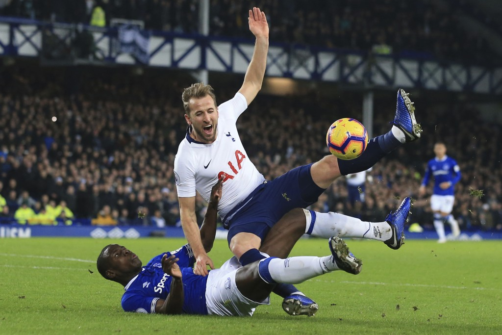 Everton's Kurt Zouma, left, and Tottenham's Harry Kane vie for the ball during the English Premier League soccer match between Everton and Tottenham a