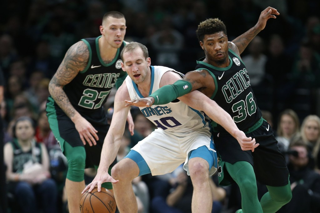 Boston Celtics' Daniel Theis (27) and Marcus Smart (36) defends against Charlotte Hornets' Cody Zeller (40) during the first half of an NBA basketball...