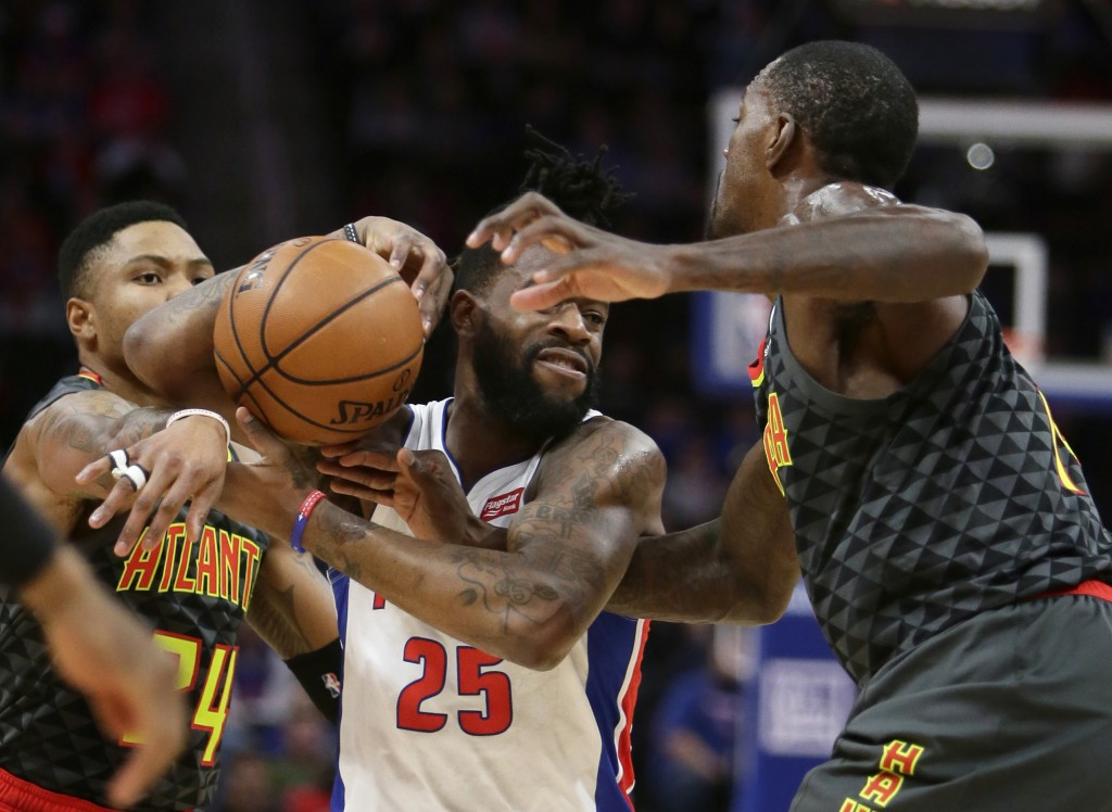 Detroit Pistons guard Reggie Bullock (25) has the ball knocked away by Atlanta Hawks center Dewayne Dedmon, right, and guard Kent Bazemore (24) during...