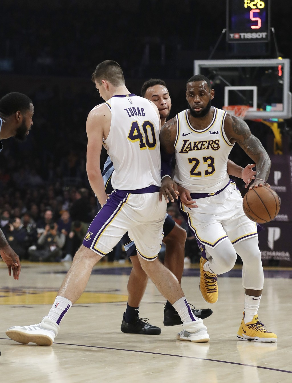 Los Angeles Lakers' LeBron James (23) dribbles around a screen set up by teammate Ivica Zubac (40) on Memphis Grizzlies' Kyle Anderson, center, during...