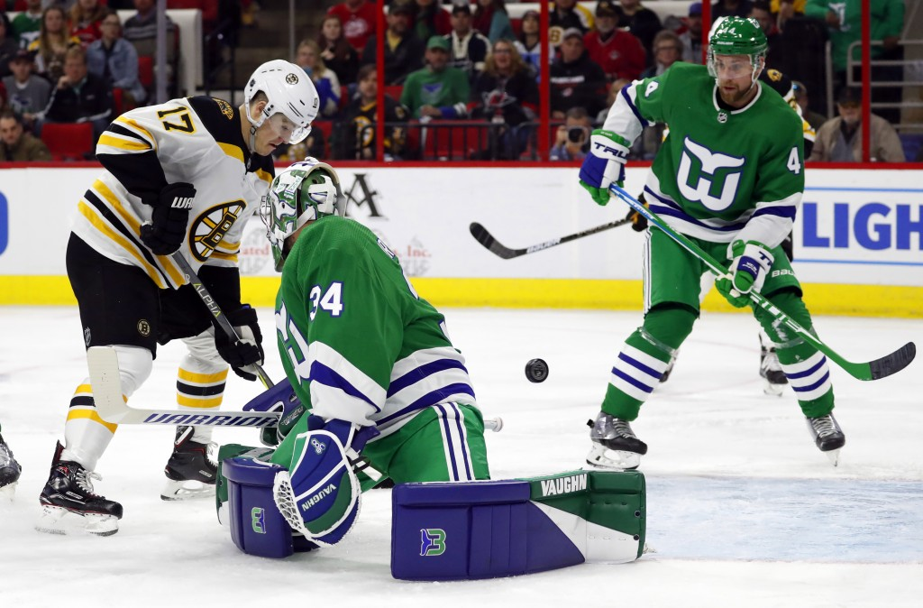 Boston Bruins' Ryan Donato (17) pushes the puck past Carolina Hurricanes goaltender Petr Mrazek (34) with Calvin de Haan (44) nearby during the first ...