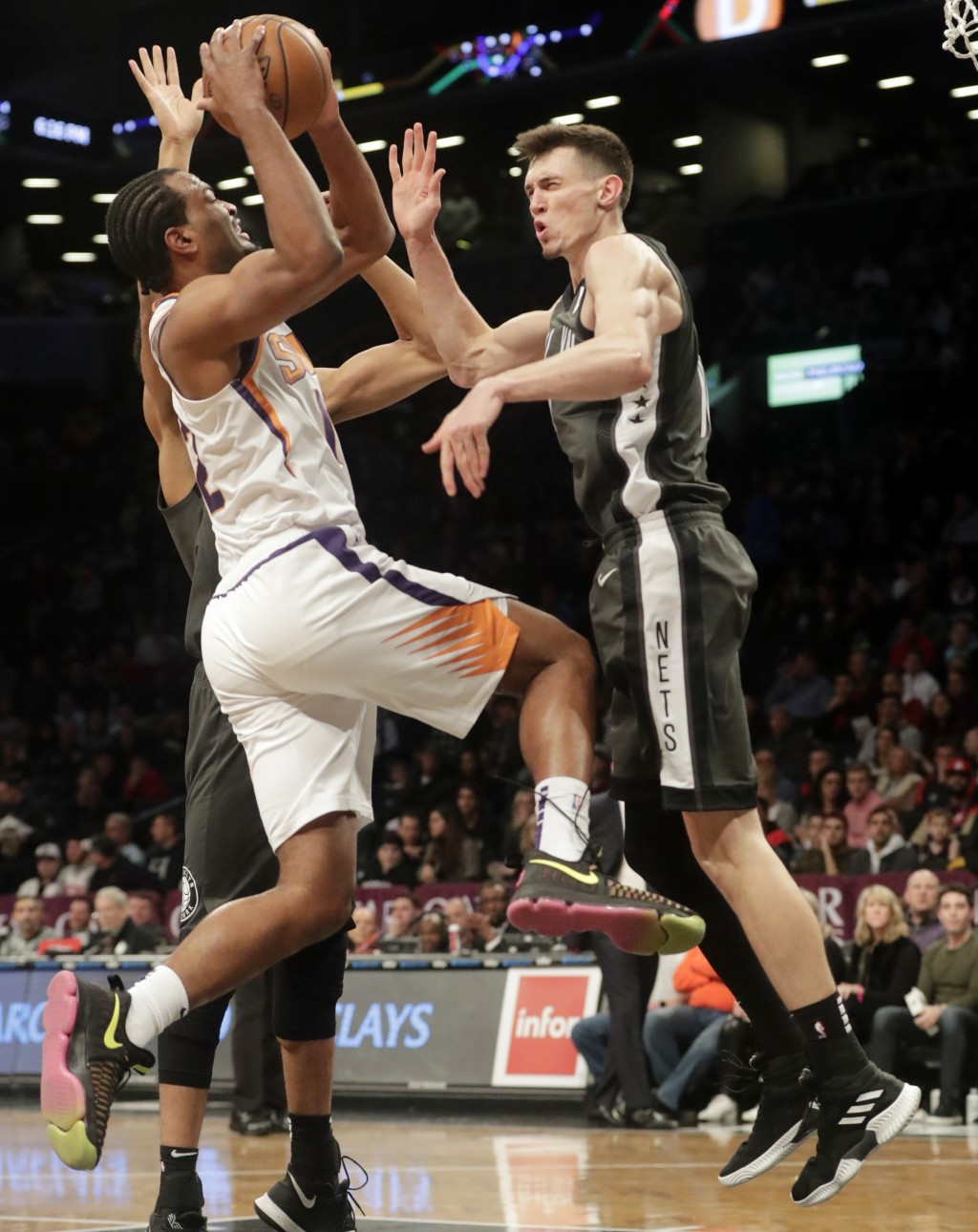 Phoenix Suns' Kelly Oubre Jr., left, drives past Brooklyn Nets' Rodions Kurucs during the first half of an NBA basketball game Sunday, Dec. 23, 2018, ...