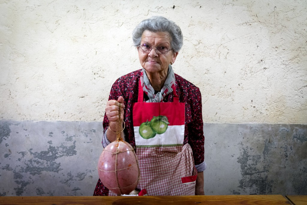 In this photo taken on Nov. 24, 2018, Francisca holds a sobrasada, a raw cured sausage, made of pork bladder during the annual pig slaughter near Petr...