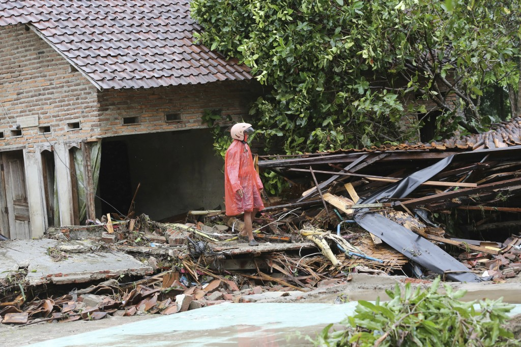 A resident inspects his house damaged by a tsunami, in Sumur village, Indonesia, Monday, Dec. 24, 2018. The tsunami apparently caused by the eruption ...