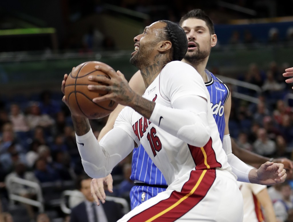 Miami Heat's James Johnson (16) goes to the basket for a shot against Orlando Magic's Nikola Vucevic, back right, during the first half of an NBA bask