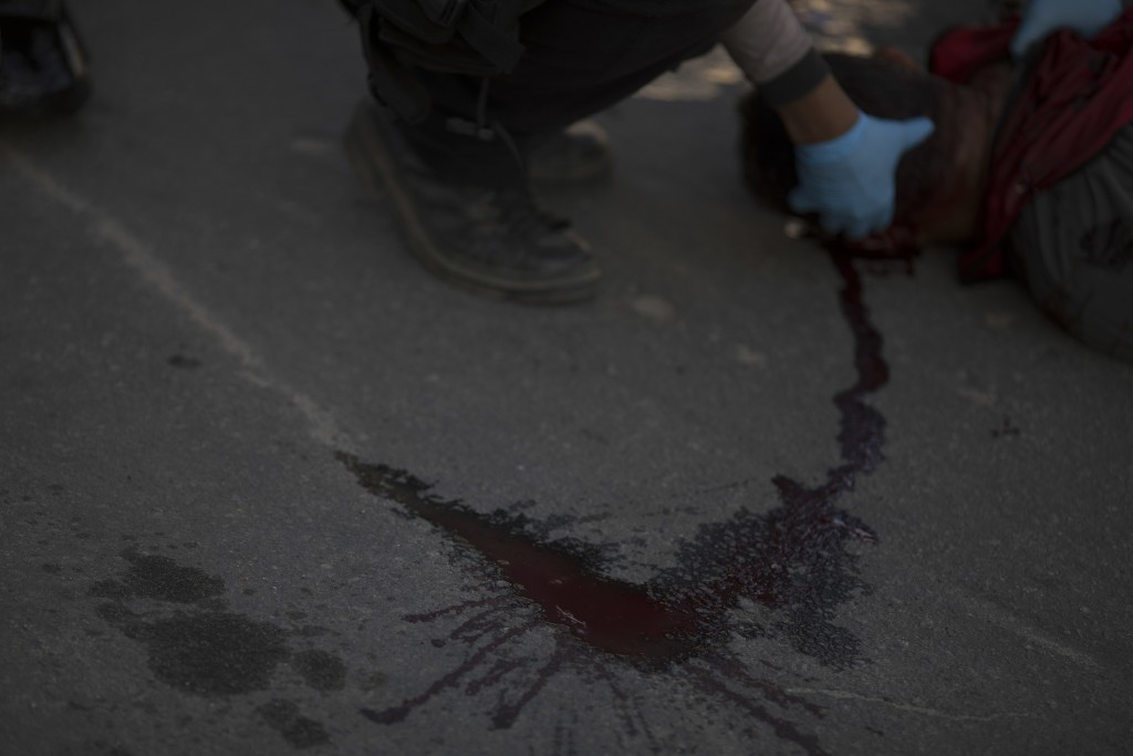 In this Sept. 1, 2018 photo, blood covers the street where a motorcycle taxi driver was found shot dead as a forensic police officer inspect the body ...